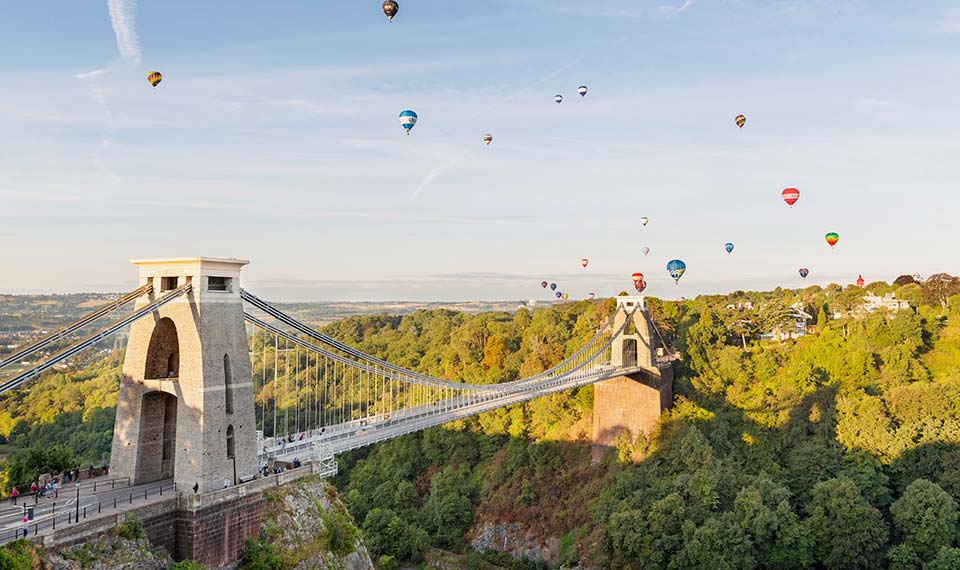 Clifton Suspension Bridge with hot air balloons in the sky above
